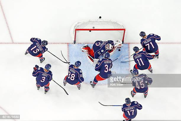 Curtis McElhinney of the Columbus Blue Jackets is surrounded by his teammates while warming up prior to the start of the game against the Montreal...
