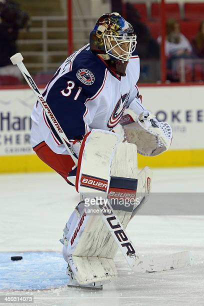 Curtis McElhinney of the Columbus Blue Jackets warms up prior to a game against the Carolina Hurricanes at PNC Arena on December 23 2013 in Raleigh...