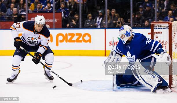 Curtis McElhinney of the Toronto Maple Leafs makes a save on Milan Lucic of the Edmonton Oilers during the third period at the Air Canada Centre on...