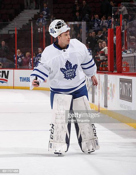 Curtis McElhinney of the Toronto Maple Leafs tosses a souvenir puck to a fan as he is named the first star of the game after a win against the Ottawa...