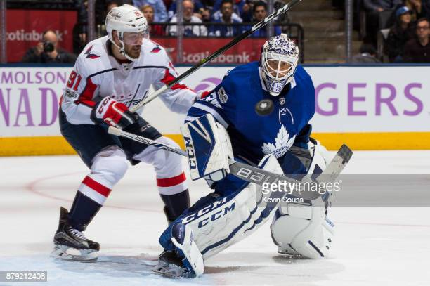 Curtis McElhinney of the Toronto Maple Leafs watches the puck as Tyler Graovac of the Washington Capitalsm works around the crease during the third...