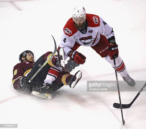 Curtis McKenzie of the Chicago Wolves gets dumped to the ice by Josiah Didier of the Charlotte Checkers during game Five of the Calder Cup Finals at...