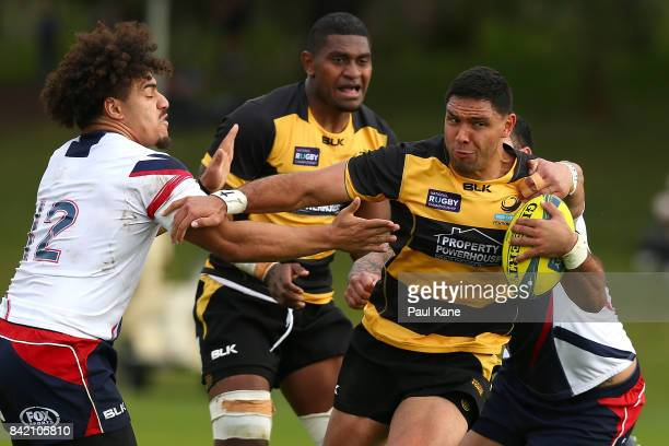 Curtis Rona of the Spirit looks to break from a tackle by Sione Tuipulotu and Lloyd Johansson of the Rising during the round one NRC match between...