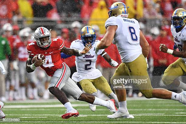 Curtis Samuel of the Ohio State Buckeyes eludes the defense of Jesse Brubaker of the Tulsa Hurricane as he picks up 18 yards in the third quarter at...