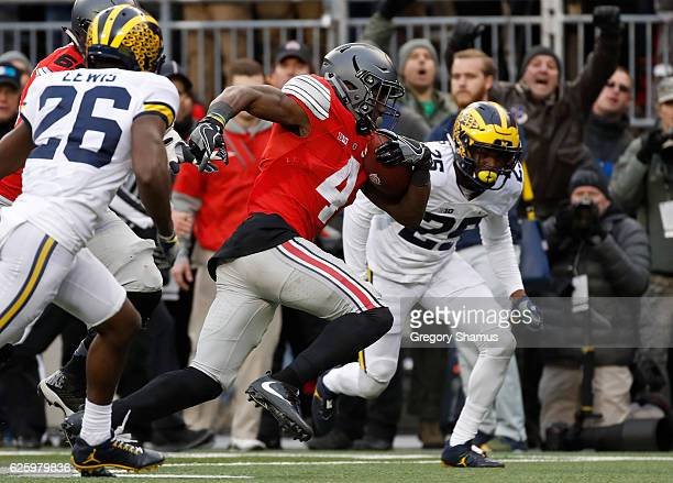 Curtis Samuel of the Ohio State Buckeyes rushes the ball to the end zone to score the gamewinning touchdown in overtime against the Michigan...