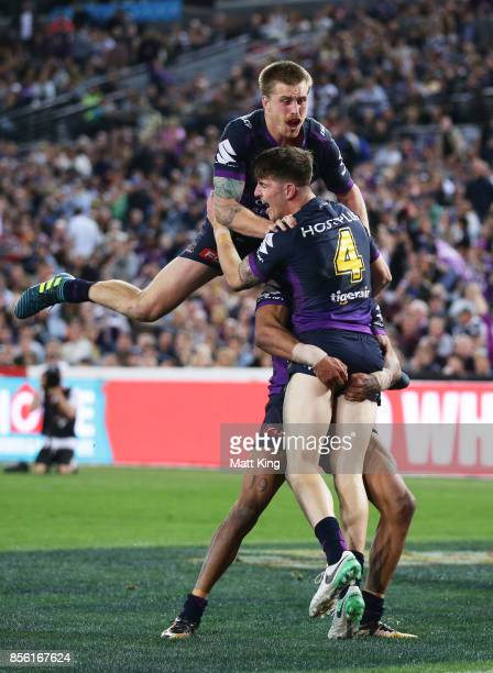 Curtis Scott of the Storm celebrates with team mates after scoring a try as Cameron Munster of the Storm jumps over the top during the 2017 NRL Grand...