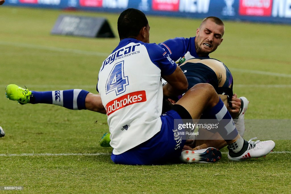 Curtis Scott of the Storm is stopped on the line by Will Hopoate and Kieran Foran of the Bulldogs during the round one NRL match between the Canterbury Bulldogs and the Melbourne Storm at Optus Stadium on March 10, 2018 in Perth, Australia.