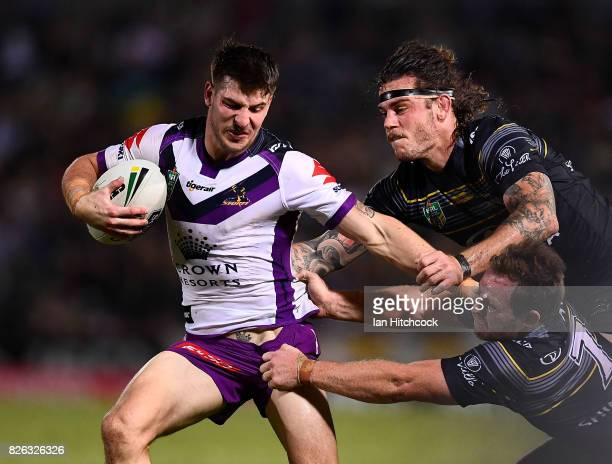 Curtis Scott of the Storm is tackled by Ethan Lowe and Michael Morgan of the Cowboys during the round 22 NRL match between the North Queensland...
