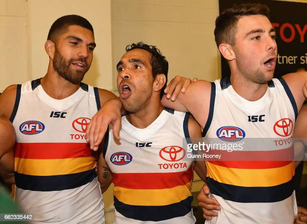 Curtly Hampton Eddie Betts and Rory Atkins of the Crows sing the song after winning the round two AFL match between the Hawthorn Hawks and the...