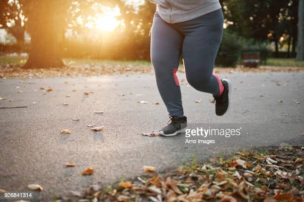 curvaceous young female runner running in park, waist down - gordo fotografías e imágenes de stock