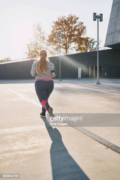 curvaceous young female runner running, rear view - fat blonde women stock pictures, royalty-free photos & images
