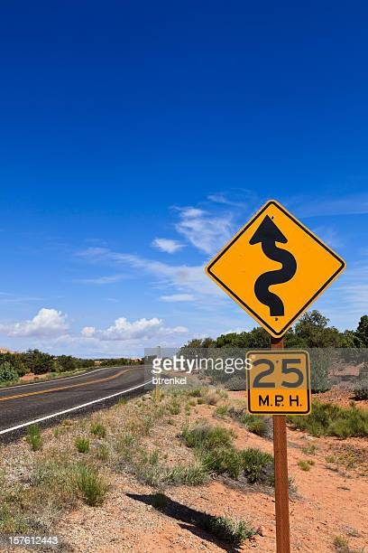 curve ahead - speed limit sign stock photos and pictures