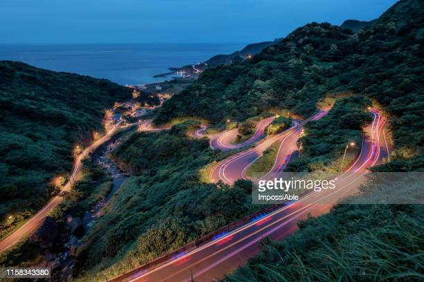 curve of coastline road heading to the ocean with lighttrail of car at twilight blue hour, taiwan - impossiable stock pictures, royalty-free photos & images