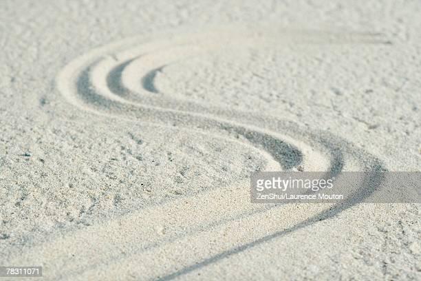 curve pattern traced into sand - letra s fotografías e imágenes de stock