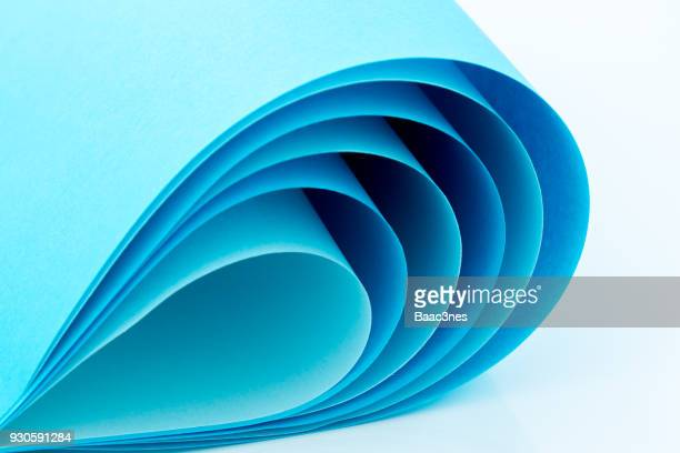 curved blue paper on a white table - 物の形 ストックフォトと画像