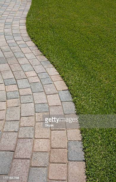 A curved brick pathway along some grass