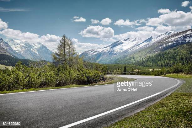 curved empty road on mountain pass, san bernardino, switzerland - strada foto e immagini stock