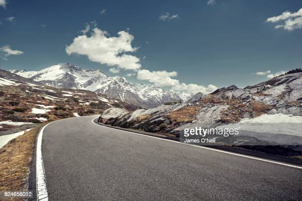 curved empty road on mountain pass, san bernardino, switzerland - mountain road stock pictures, royalty-free photos & images