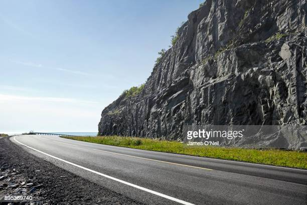 Curved empty road with rocky cliff