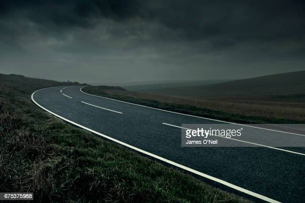curved road through stormy landscape - 人気のない道路 ストックフォトと画像