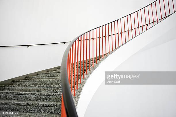 curved stairs with red banister - veiligheidshek stockfoto's en -beelden