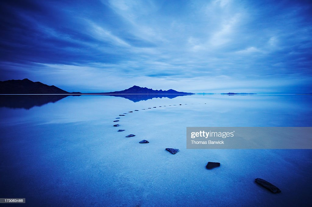 Curved stone pathway in calm lake at sunrise : Stock Photo