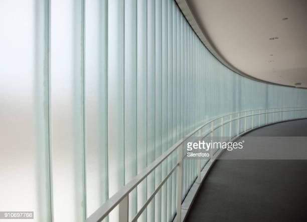 curving sweep of a glass sided corridor - bogen architektonisches detail stock-fotos und bilder