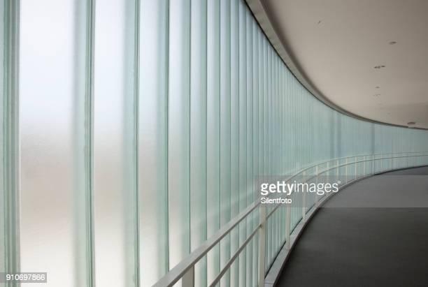 curving sweep of a glass sided corridor - うねのある ストックフォトと画像
