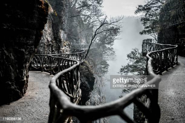 a curving walkway with branch-like security railing on the cliffside of a tianmen mountain (天门山) in the zhangjiajie (张家界) - tianmen stock pictures, royalty-free photos & images
