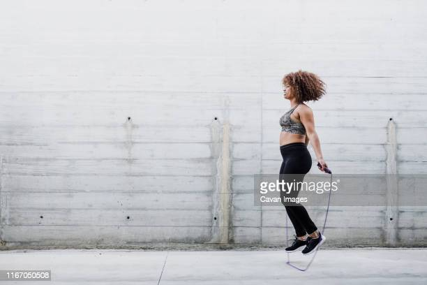 curvy african american woman skipping rope in urban area - curvy women stock pictures, royalty-free photos & images