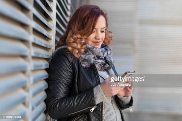 bochtige echte vrouw leunend op muur kijkt naar de telefoon en surft het internet op een winterdag - goed gekleed stockfoto's en -beelden