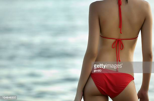 curvy sexy back of a curvy red bikini model. - beautiful asian legs stock photos and pictures