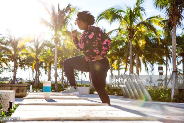 Curvy young black woman exercising, having sport training in the city public park