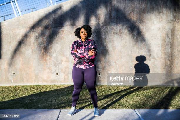 curvy young black woman exercising, having sport training in the city public park - plus size model stock photos and pictures