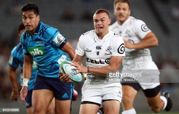 Curwin Bosch of the Sharks breaks away from Reiko Ioane of the Blues during the Super Rugby match between the Auckland Blues of New Zealand and the...