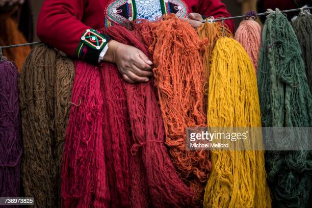 Quechuan women of Chinchero weave traditional clothes in traditional ways for sale.