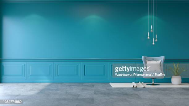 cushion of chair by blue wall at home - muur stockfoto's en -beelden