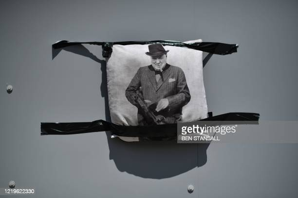 A cushion with a portrait of former Prime Minister Winston Churchill is seen on the cladding around his statue as members of far right groups gather...