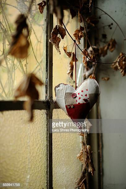 cushioned heart hung by window with dried leaves - lucy shires stock pictures, royalty-free photos & images