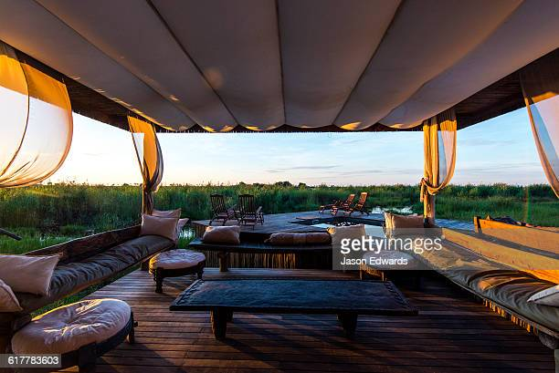 Cushions and sofas in a lounge beneath a canopy in a luxury safari camp.