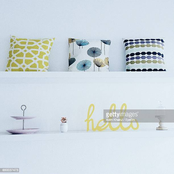 Cushions And Text On Shelves Against Wall At Home