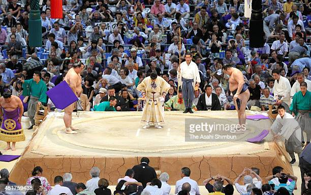 Cushions are flown toward the ring after Mongolian yokozuna Kakuryu is defeated by ozeki Kisenosato during day thirteen of the Grand Sumo Nagoya...