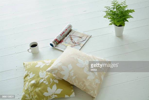 cushions, magazine, cup of coffee and potted plant on floor - glass magazine stock photos and pictures