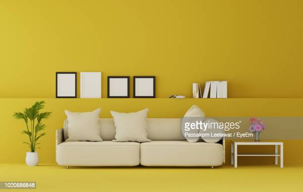 cushions on sofa against yellow wall at home - gelb stock-fotos und bilder