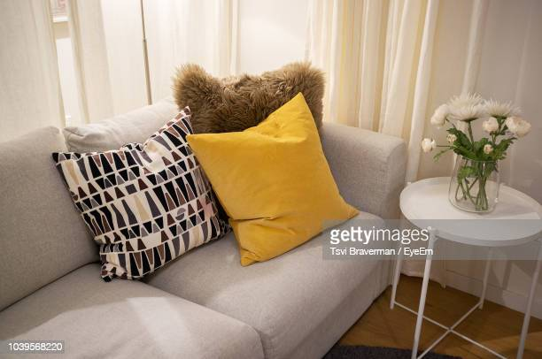 cushions on sofa by vase at home - cushion stock photos and pictures