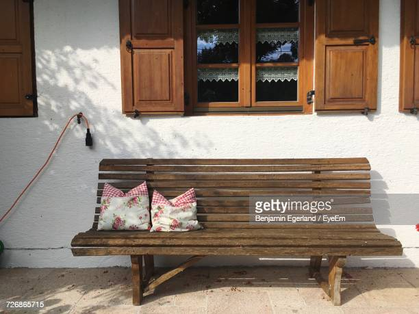 Cushions On Wooden Bench Against Window Outside House