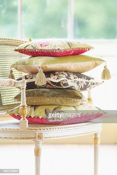Cushions pilled on stylish chair in bright room.