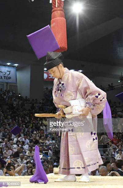 Cushions thrown by spectators in appreciation for Tochinoshin's defeat of yokozuna Kisenosato just miss a referee standing on the dohyo on July 11...