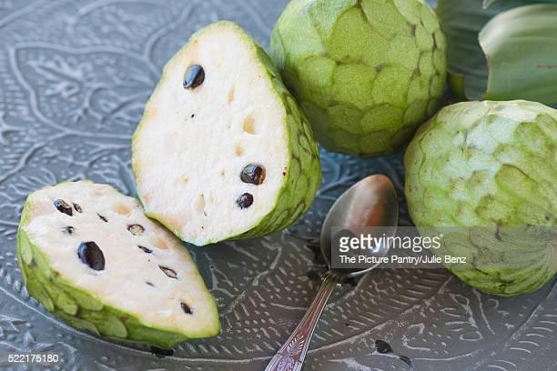 custard fruit on metal tray, whole and cut, with teaspoon