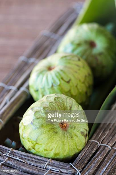 custard fruit within wood and metal box, on rustic woven mat